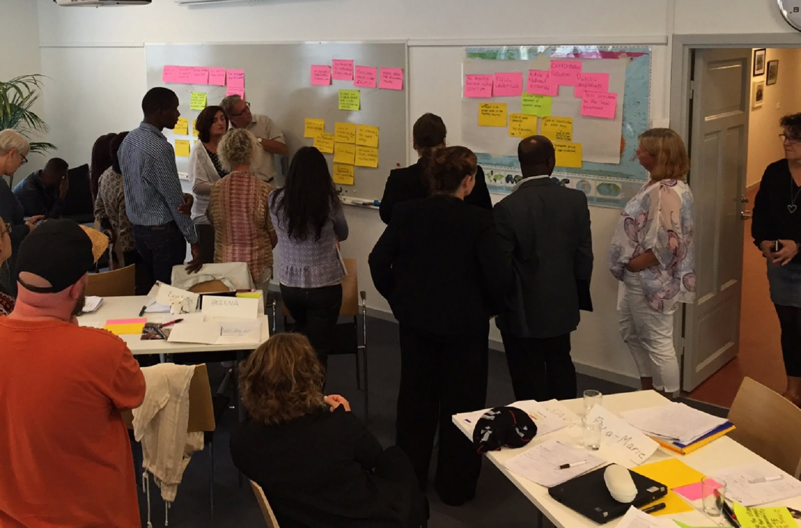 people standing analysing their problem trees on post its on wall in conference room